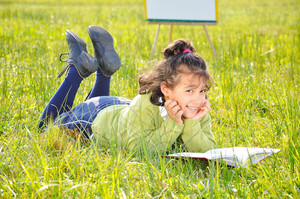Cute girl reading on meadow with board behind
