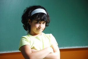 Cute girl standing in front of board in classroom