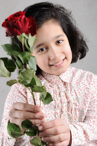 Cute girl with a beautiful red rose in her hands