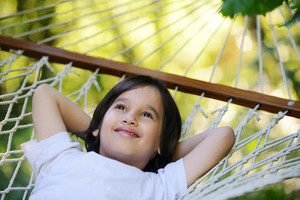 Cute kid lying in hammock at beautiful summer day
