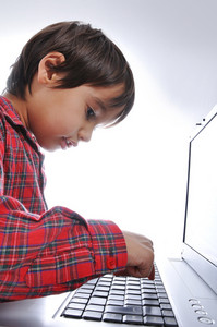 Cute kid sitting with laptop