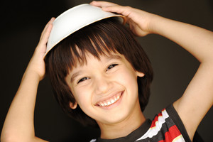 Cute kid with dish on head smiling