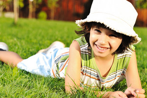 Cute kid with hat on head laying on grass in park