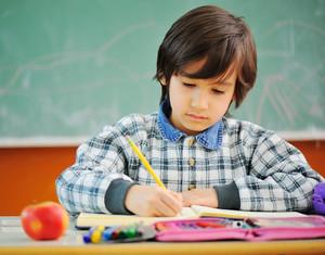 Cute little boy in school in front of blackboard