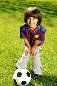 Cute little boy playing with a ball in beautiful park in nature