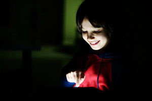 Cute little boy playing with tablet pc in dark room at home