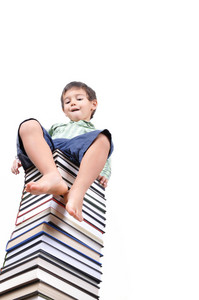 Cute little boy sitting on a large pile of books
