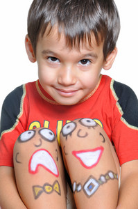 Cute little boy with painted smileys on his legs