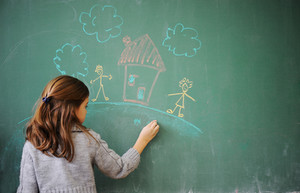 Cute little girl drawing on blackboard