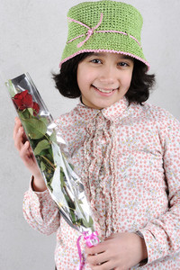 Cute little girl holding red rose
