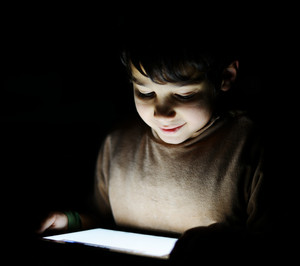 Cute little kid playing with tablet pc in dark room at home