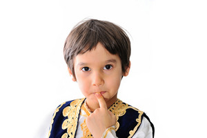 Cute little kid wearing traditional clothes holding a finger on his lips