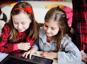可愛的可愛的小學生在與筆記本電腦有clasroom教育活動