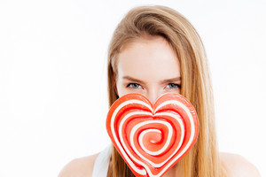 Cute lovely young woman covered face with heatr shaped lollipop over white background
