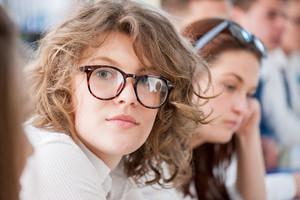 Cute schoolgirl with glasses posing in a schoolroom