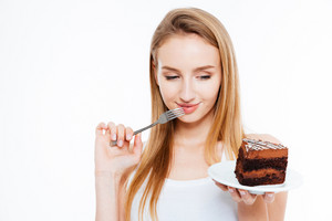 Cute thoughtful young woman thinking and holding fork and piece of cake over white background