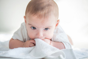 Cute toddler lying on a white towel