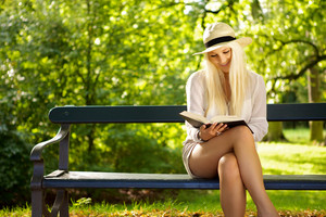 Cute woman sitting on a bench in a park reading a book. Copyspace left.