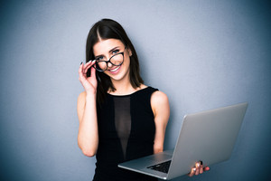 Cute woman with laptop and glasses looking at camera