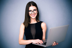 Cute woman with laptop standing over gray background