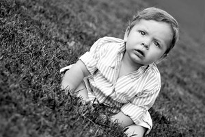 Cute young baby sitting in the grass in black and white.