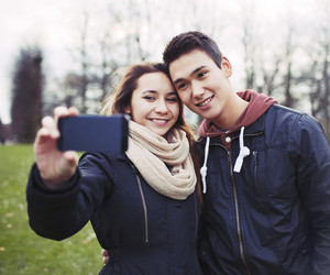 Cute young couple looking happy while taking pictures using a smart phone at the park. Mixed race teenage boy and girl in love photographing themselves outdoors.