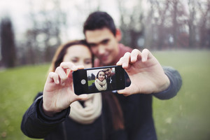 Cute young couple taking a self-portrait with a cell phone at the park. Mixed race teenage man and woman outdoors taking their picture with smartphone.