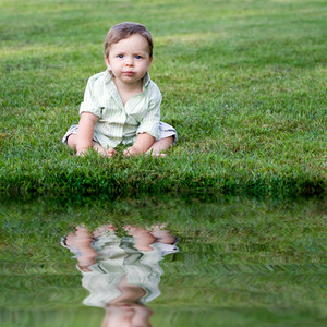 Cute young infant sitting in the grass all alone.