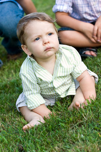 Cute young infant sitting in the grass with his brother and sister.