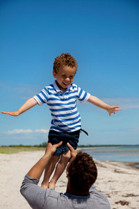 Dad lifting his young son against the bright summer sky