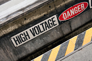 Danger high voltage warning sign with black and yellow hazard stripes.