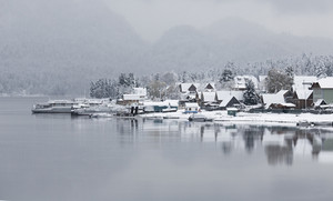 Snowy village on the edge of a foggy lake