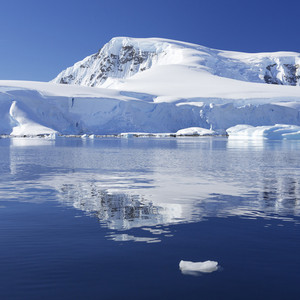 Sunlit iceberg reflected in icy waters