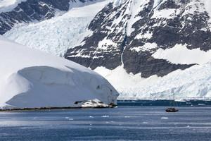 Boat traveling past a large iceberg along the coast