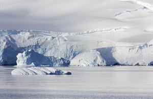 Ice floe and a snowy, sunlit coast