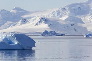 Iceberg and a snowy, sunlit coast