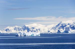 Snowy coast and iceberg under a blue sky
