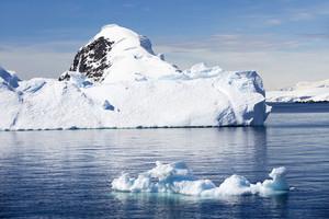 Snowy coast and ice floe under a blue sky
