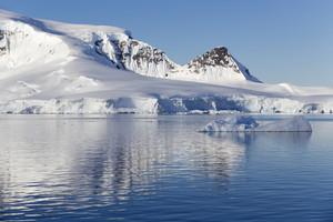 Sunlit, snowy coast and ice floe under a blue sky
