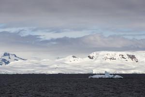 Snowy coast and ice floe under a grey sky