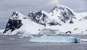 Snowy, rocky coast and iceberg under a stormy sky