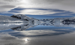 Sunlit, snowy coast reflected under a cloudy sky