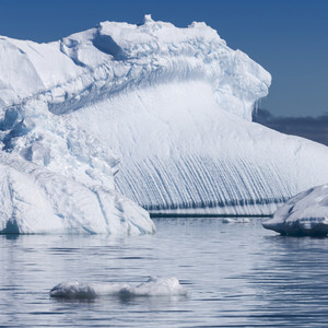 Close up of a sunlit iceberg under a blue sky
