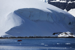 Boat traveling past a sunlit, snowy coast