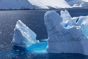 Sunlit iceberg along the snowy coast