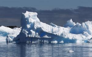 Sunlit iceberg under a stormy sky