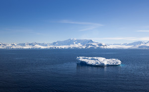 Sunlit ice floe along a snowy coast