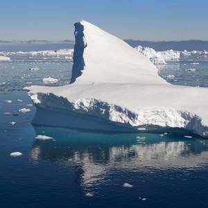 Sunlit ice floe and iceberg