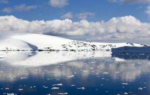 Sunlit, snowy coast reflected under a blue sky