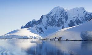Sunlit, snowy coast under a blue sky